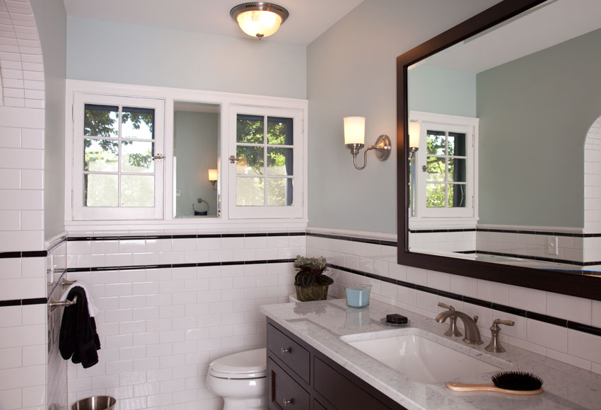 Built in 1930, this classic Tudor home looks fresh and clean after its recent renovation. The guest bathroom includes a custom vanity with a carrera marble top, subway tile, and a heated floor.