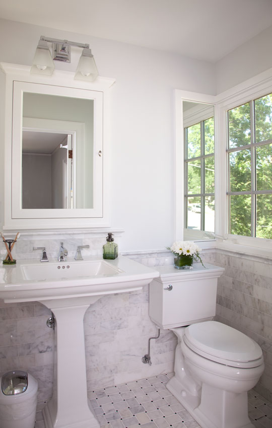 Built in 1930, this classic Tudor home looks fresh and clean after its recent renovation. The exterior wall of the master bathroom was moved out 16″, making it a more comfortable size. Letoon wainscoting and a carrera marble basket weave pattern on the floor give this bath a rich aesthetic.