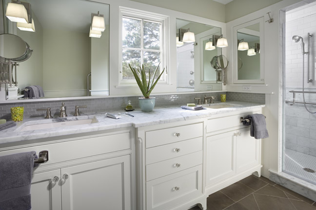 <p>This home was completely renovated, including an addition. It was transformed from a Colonial style to Greek Revival, which was more fitting for the neighborhood. This bathroom features a custom double vanity with a carrera marble top. The shower includes carrera marble and subway tile.</p>