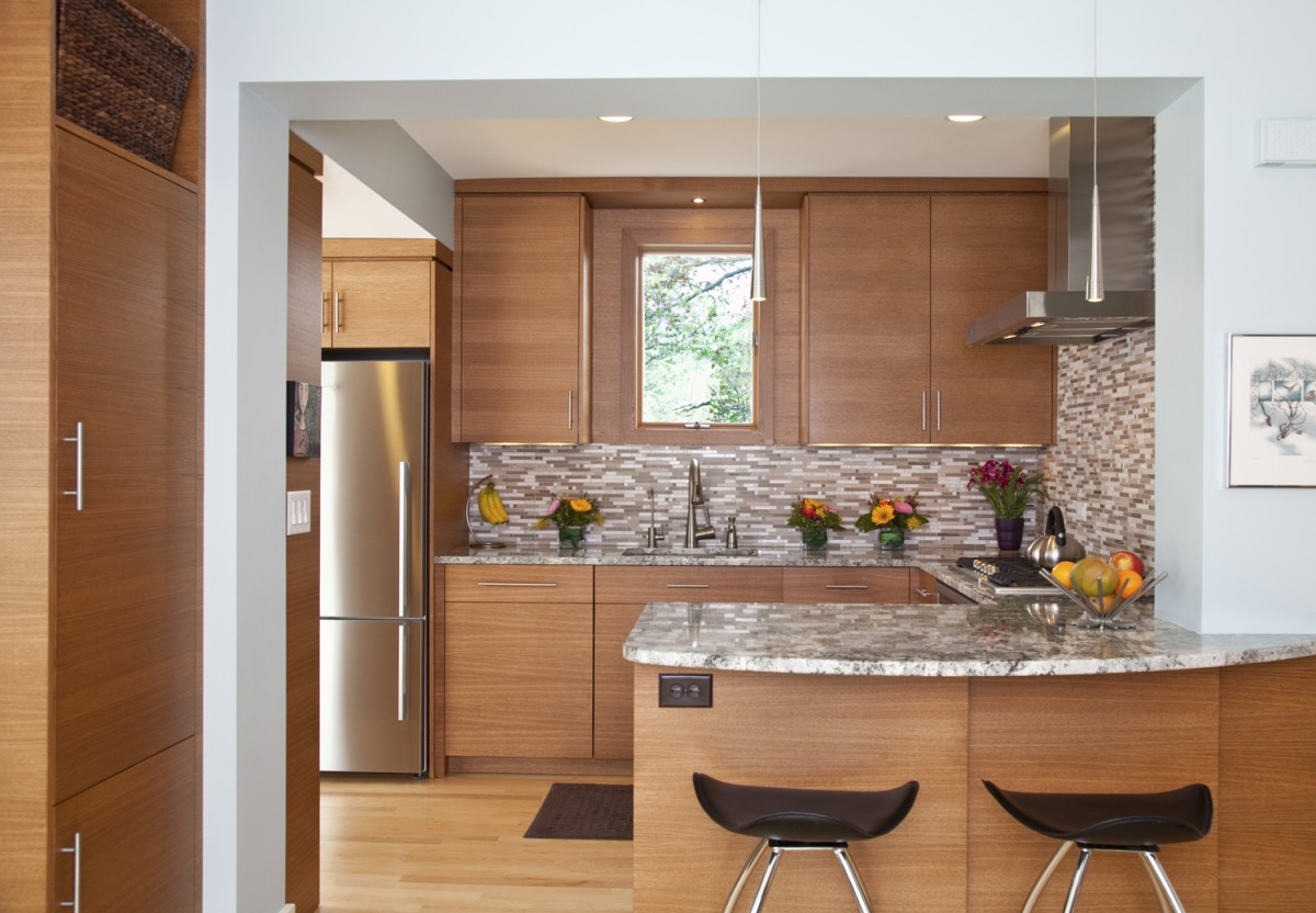 The opening to the kitchen was widened, providing a dramatic view of the horizontal-grain oak cabinets in the kitchen. It also provides seating at the peninsula, and the J-shaped countertop doubles kitchen work space.