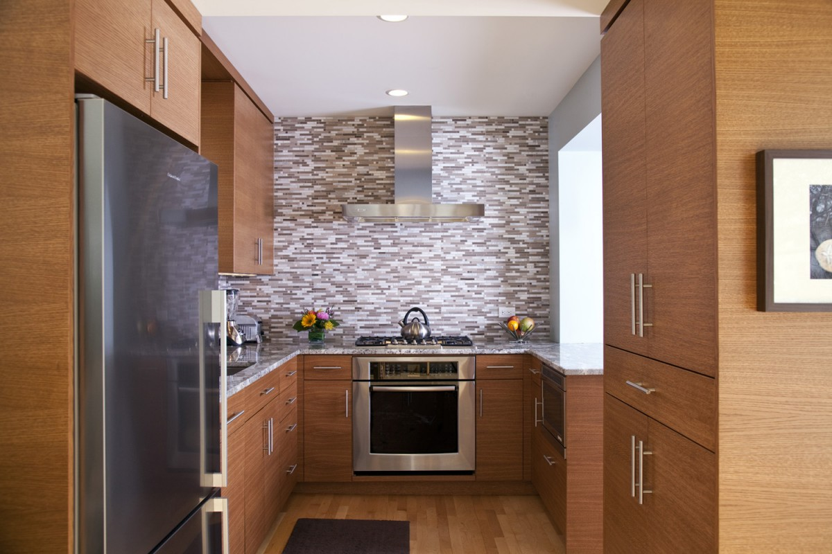 In this project, we opened up the wall between the kitchen and living room, making both spaces feel bigger. The J-shaped countertop more than doubles the counter space of the previous kitchen without the need for an addition. The rift-cut horizontal-grain oak cabinets and tile backsplash add the contemporary flair that our clients desired. The natural materials (oak, granite) warm up the space. New cabinetry matching the kitchen was built into the living room, making the two rooms feel unified.