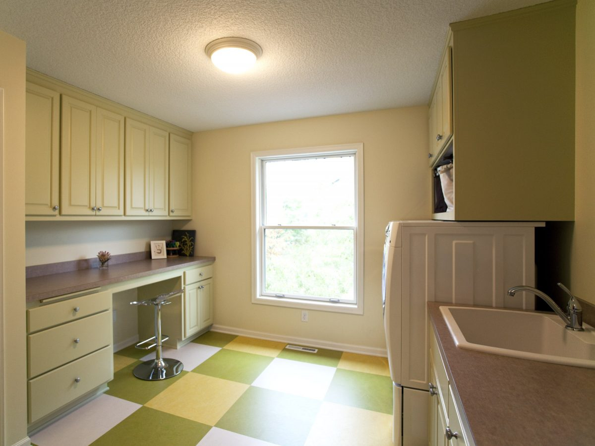 <p>For the laundry room, TreHus repurposed the original maple kitchen cabinets by painting them light green for a little added personality. Now there is room for laundry workspace, and a counter and desk area on the other side of the room for crafts.</p>
