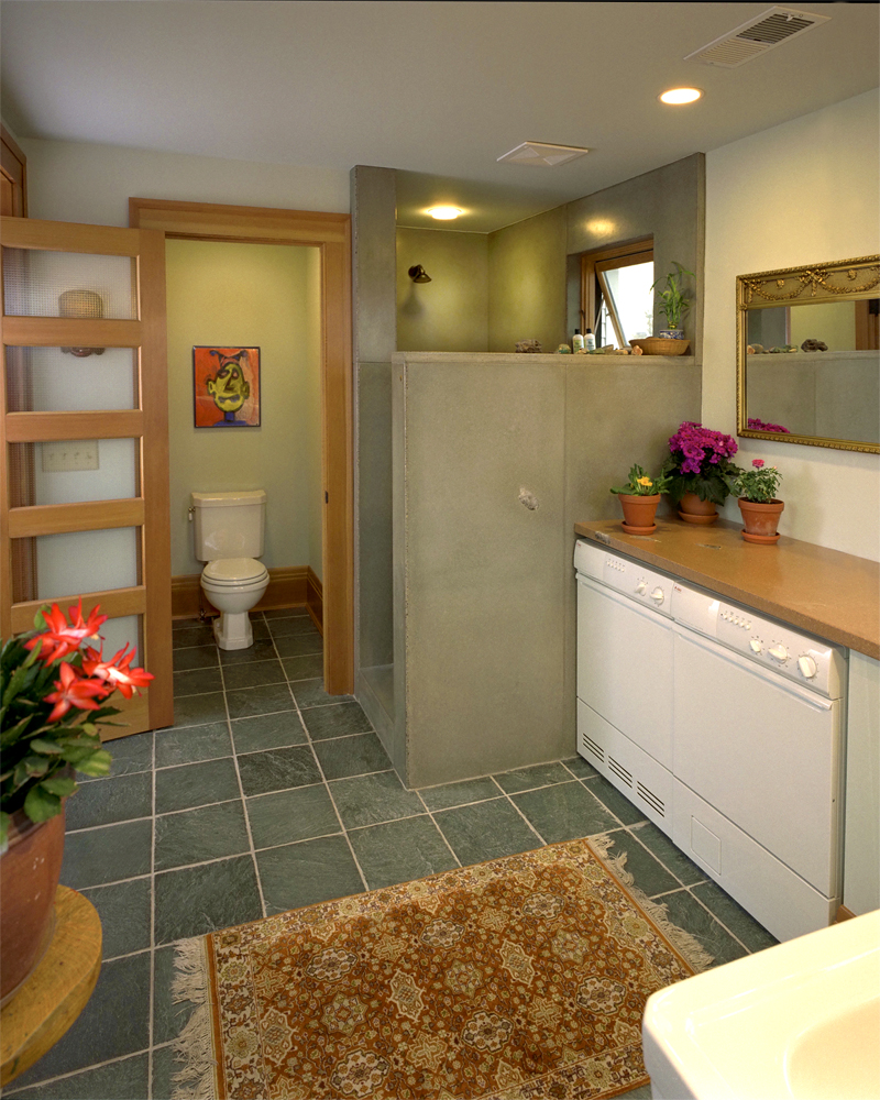 <p>The master bathroom, which includes a cement shower and countertop, and laundry machines.</p>