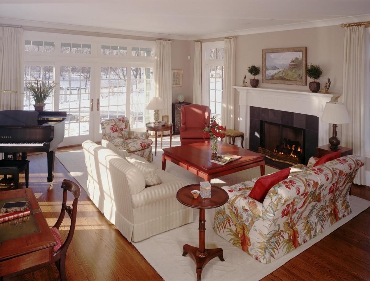 <p>The sense of comfort in this living room is heightened by the beautiful views and natural light provided by the large windows and french doors that lead out to Lake of the Isles. For days inside, the woodburning fireplace and clean, white woodwork make this remodeled living room feel cozy and warm.</p>