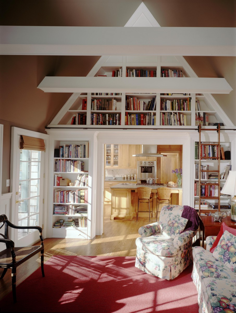 The doorway from the sitting room to the kitchen is surrounded by bookshelves, with a sliding ladder providing access to shelves toward the top of the vaulted ceiling. The bookshelves provide efficient storage and a beautiful architectural detail.