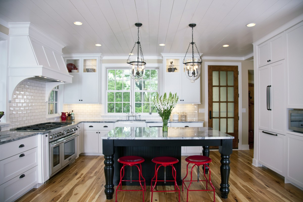 <p>Though the entire home was built in 2012-2013, our designers made it look like a historic lakeside cottage through traditional design and materials. Enameled shiplap boards are present on the ceilings throughout the first floor, as well as on some of the walls, and the floors are hickory, which adds to the old-time aesthetic. The kitchen features custom cabinetry, a traditional subway tile back splash, and plenty of seating and natural light. The owner bought metal stools and had them painted red by a car painter – we think they turned out quite nicely!</p>