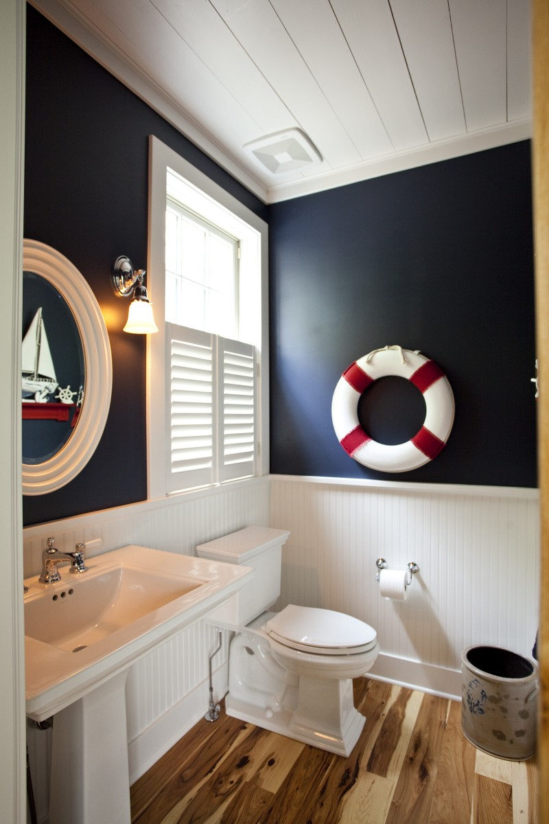 This powder room is located just off the mudroom adjacent to the kitchen. Themes from the rest of the first floor are present here as well: beadboard on the walls is reminiscent of accents on the kitchen cabinets, and the same tongue-and-groove boards that adorn the ceilings on the rest of the first floor are here as well.