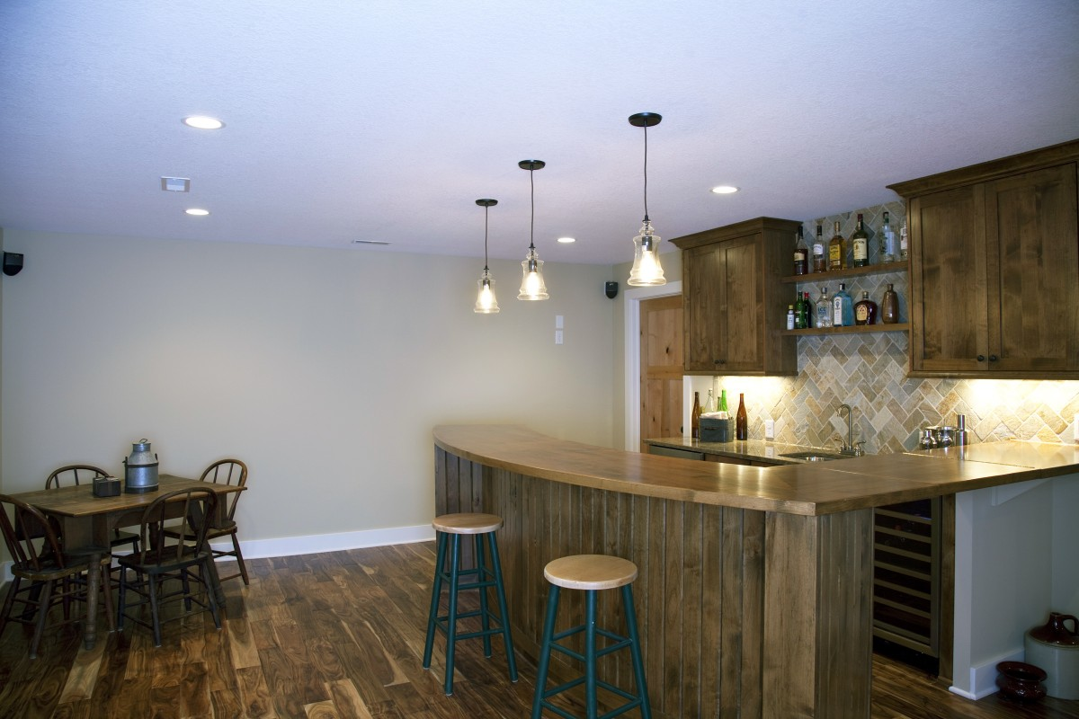 The basement wetbar is a great place guests and family members to congregate. The material selections create a warm, high-end but unpretentious feel in this room – the bar and cabinets are clear alder, the floor is hand-scraped acacia, and the backsplash is a quartzite tile.