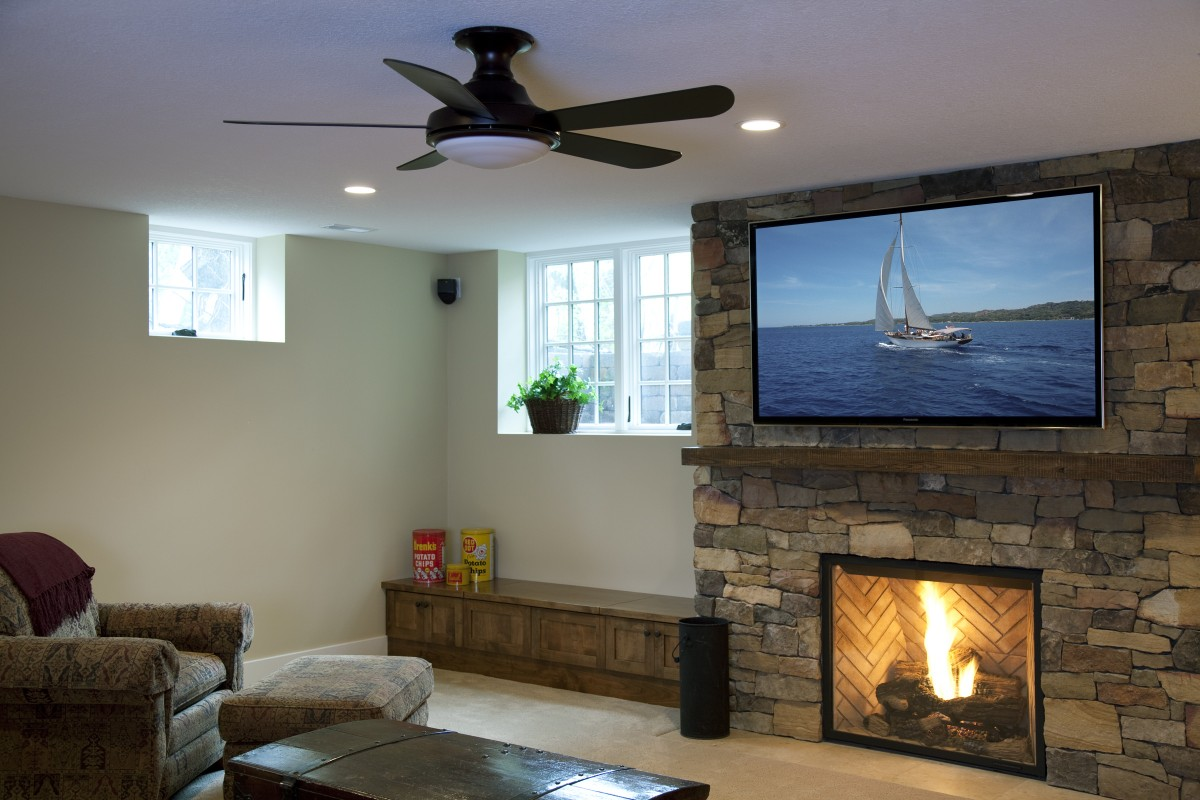 <p>The basement entertainment area centers around a beautiful stone fireplace – the stones of which were handcut on site to fit together. The stones are broken up by a reclaimed wood beam, which adds to the rustic aesthetic. To the left of the fireplace there is a large egress window, making the space feel lighter and less basement-like.</p>