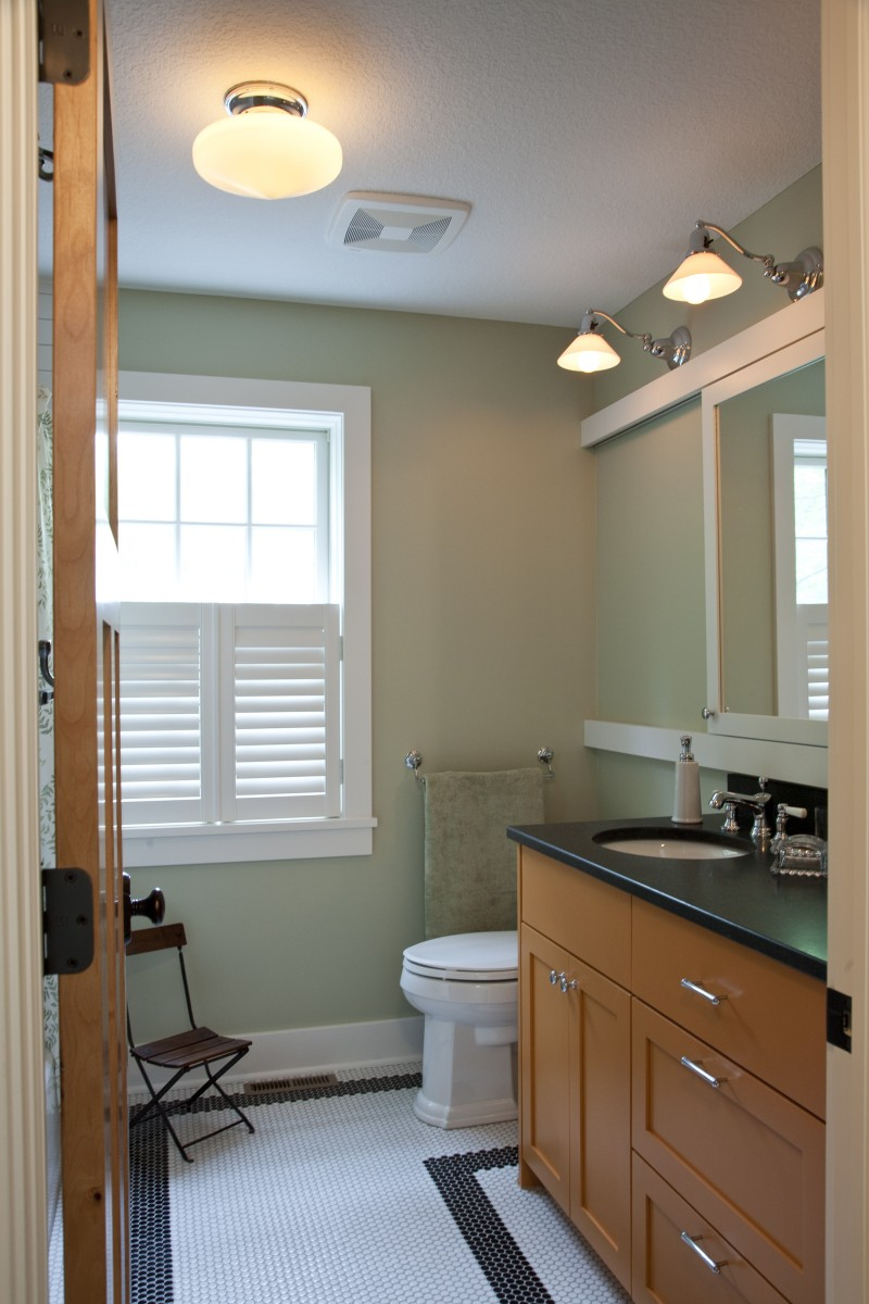 <p>This guest bathroom features a unique orange vanity with a honed granite top. Another unique feature is that the mirror hides a window – when one wants privacy, the mirror/window can be closed, and when one wants light, it can be opened. Here it is pictured closed.</p>