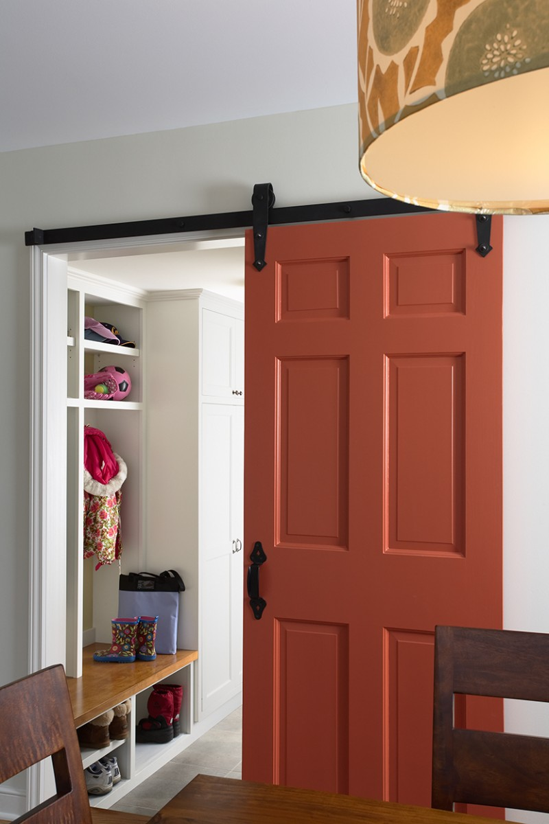 <p>A colorful barn door opens to reveal the new mudroom, which was created where a closet used to be.</p>