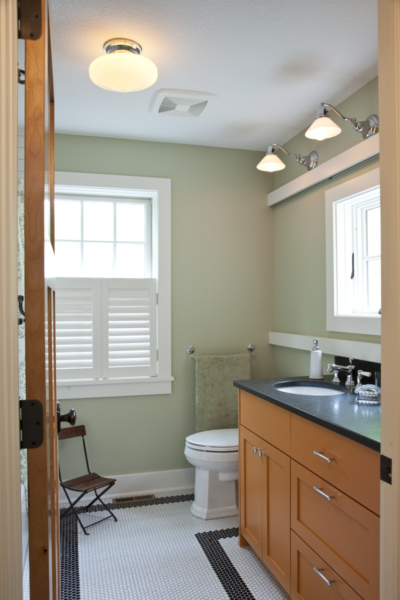 <p>This guest bathroom features a unique orange vanity with a honed granite top. Another unique feature is that the mirror hides a window – when one wants privacy, the mirror/window can be closed, and when one wants light, it can be opened. Here it is pictured open.</p>