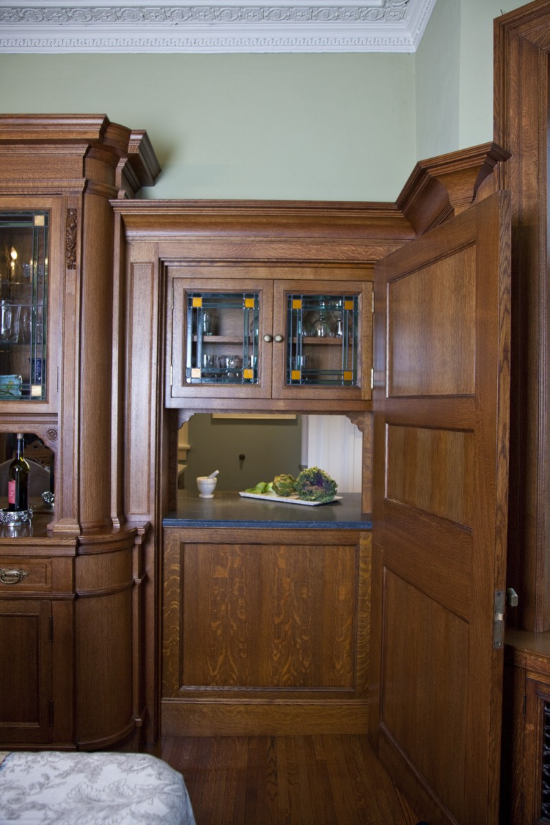 Before this project, there was a sheet of plywood behind the door. TreHus designed and built this pass-through from the kitchen to seamlessly match the rich, ornate buffet original to this 100+ year old home.  The graining, detailing and stain of the new quartersawn oak cabinet and the detailing and coloring of the new leaded glass doors match the originals exactly.