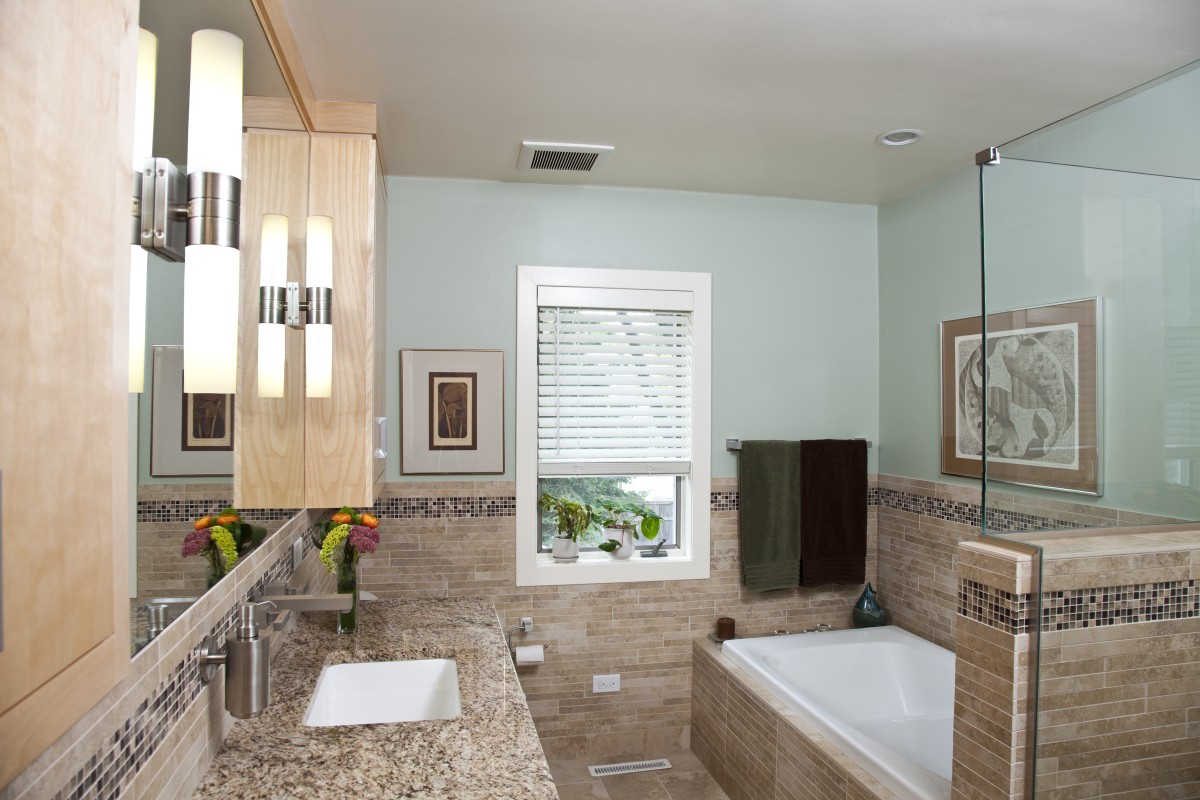 This bathroom includes plenty of storage in the vanity and in built-in cabinets on either side of the vanity. All of the cabinetry is maple, with the two tones in the vanity being achieved by staining (which you know is not easy if you have ever tried to stain maple). A decorative tile band runs all the way around the bathroom.