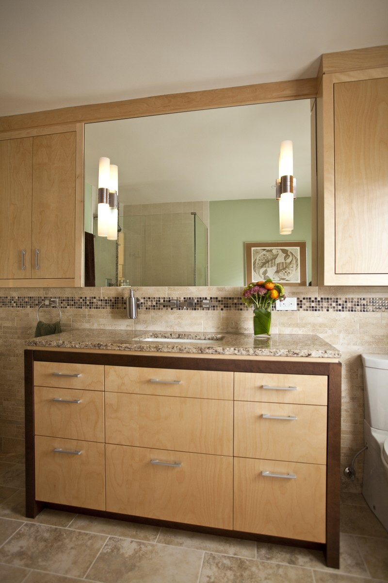 <p>Colors of nature line the inside of this bathroom remodel, bringing the outdoors in. Two different stain colors give this bath vanity a contemporary feel while showcasing the natural wood. The decorative tile band meanders its way through out the space giving it a sense of cohesion and playfulness.</p>
