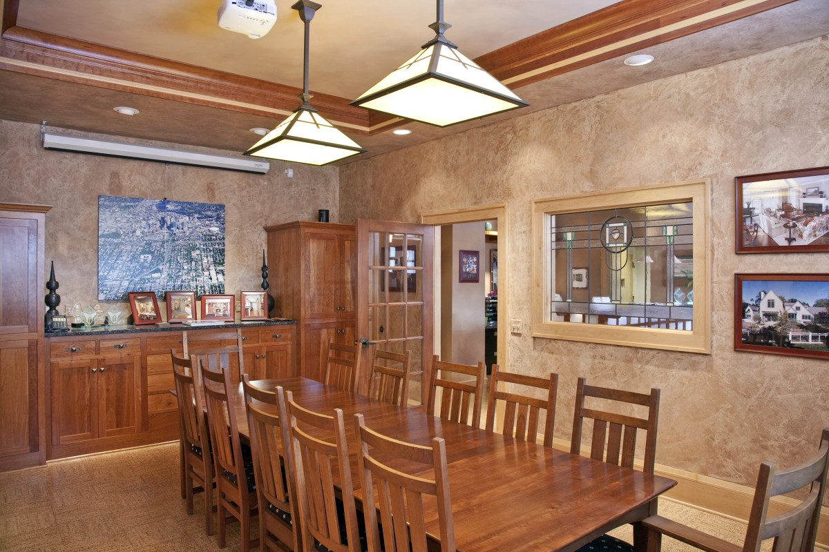 <p>The TreHus conference room features a tray ceiling accentuated by cherry molding, custom cherry cabinets, and a leaded-glass window.  Two large mission-style pendants hang from the ceiling and it is furnished with a Stickley table and chairs.</p>
