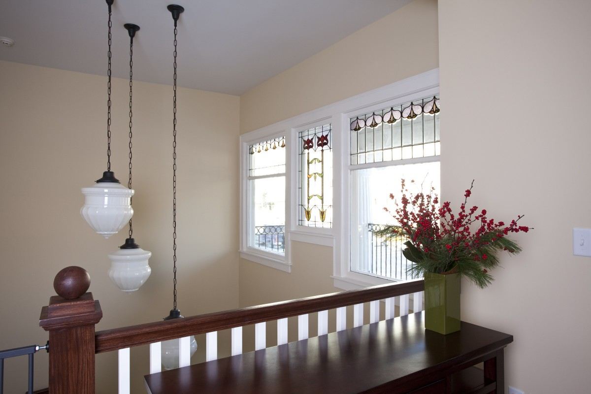 <p>Stained glass windows from around the house were salvaged and reused to let light into the entry.  Three large pendants are suspended at different heights over the tile floor below.</p>