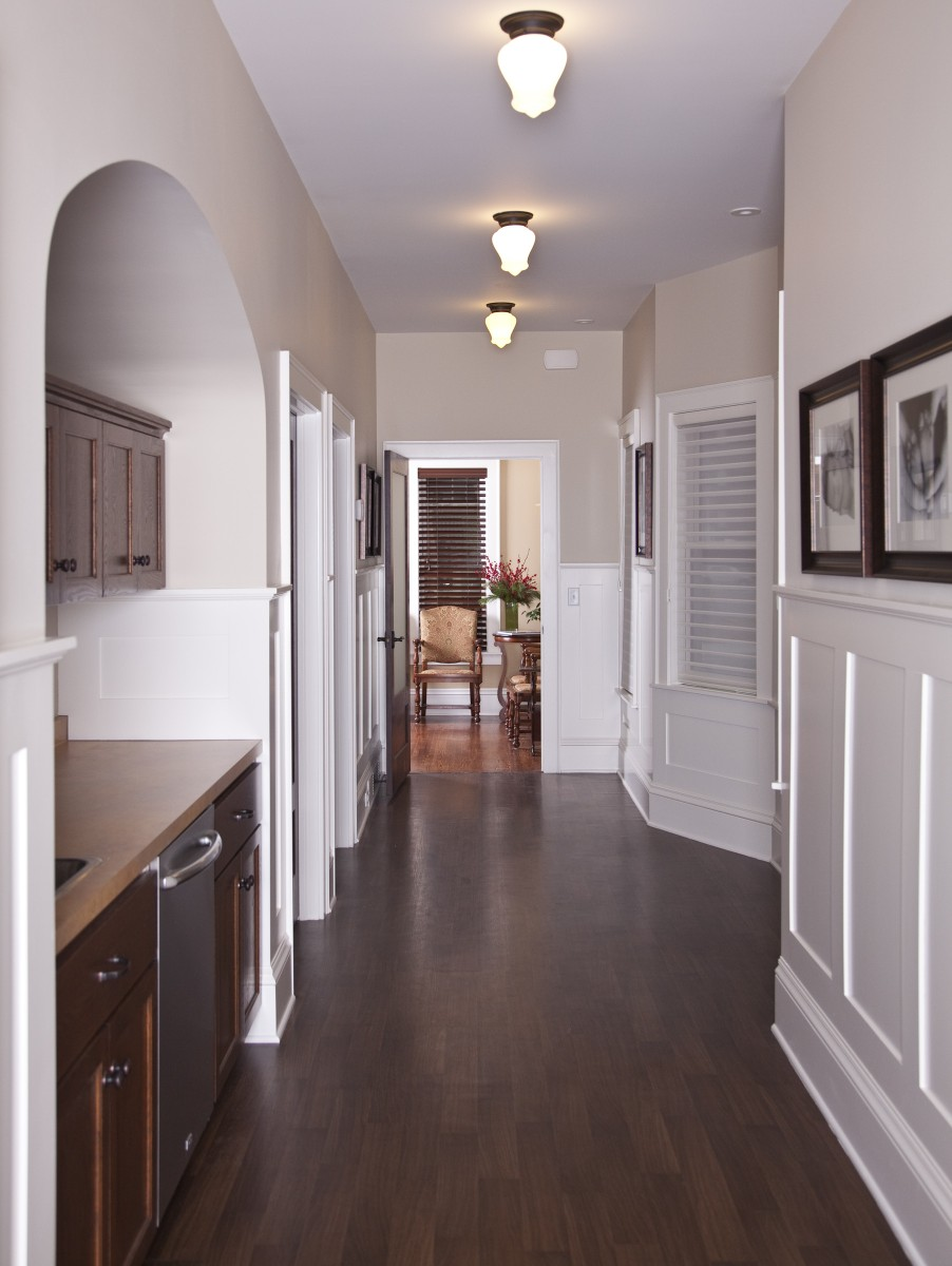 <p>The hallway where all of the work of the birth center takes place, with doors for the exam room and two suites.  The enameled wainscoting adds a light aesthetic to the space and is stylistically appropriate for the home.</p>