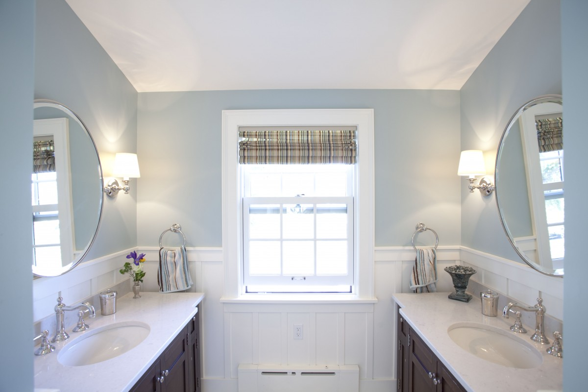 <p>This bathroom is used every morning by a busy family of six as they get ready for the day. Popping up a dormer made the bathroom much larger, and light finishes give the room a clean, cheery feeling. Details like the white painted wood wainscoting and rug inlay add visual interest, while the dueling vanities make it easy for several people to get ready for the day simultaneously.</p>