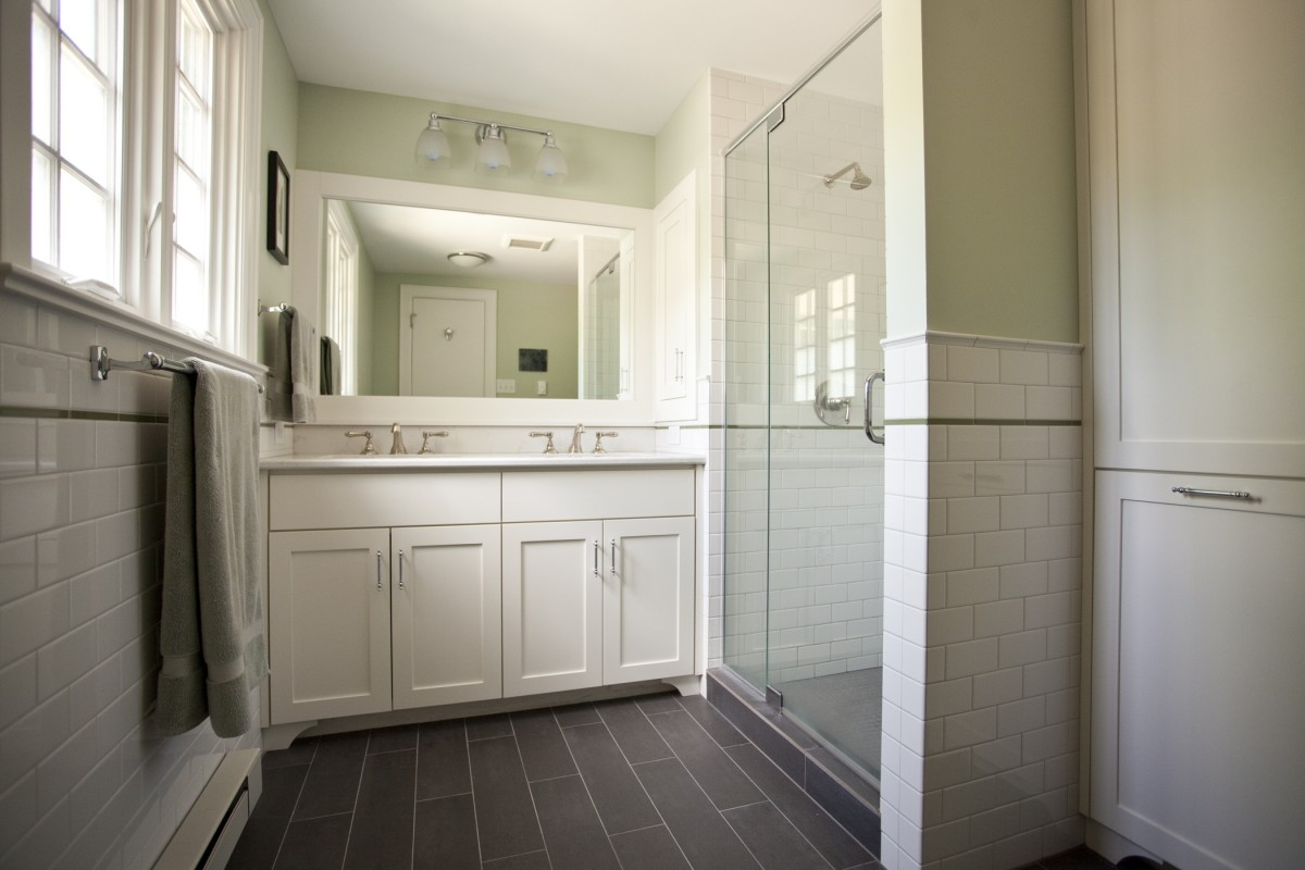 This bathroom in Minneapolis was remodeled in 2013. The gray floor gives it a clean look, and the subway tile, cap and accent band tie it into the historic house in which it resides. The vanity, medicine cabinet, and floor-to-ceiling storage cabinet help make it convenient and orderly.