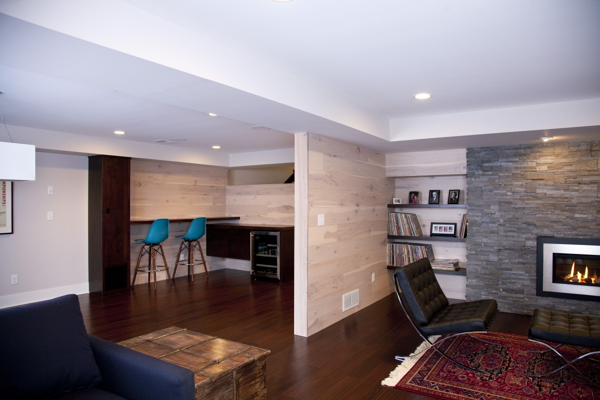 <p>The owners of this home desired to update their 1970s-style basement to fit continuously with the midcentury modern aesthetic of the rest of their home. The popcorn ceiling and old carpet were removed, and restructured duct work created an intentional design for the ceiling. New Peruvian walnut flooring and a new fireplace insert with surrounding stone create a simple, modern look in keeping with the tastes of the homeowners and style of the home. Details like the bar area and hickory wall paneling (actually flooring put on the wall!) provide them with a customized space that is uniquely their own.</p>