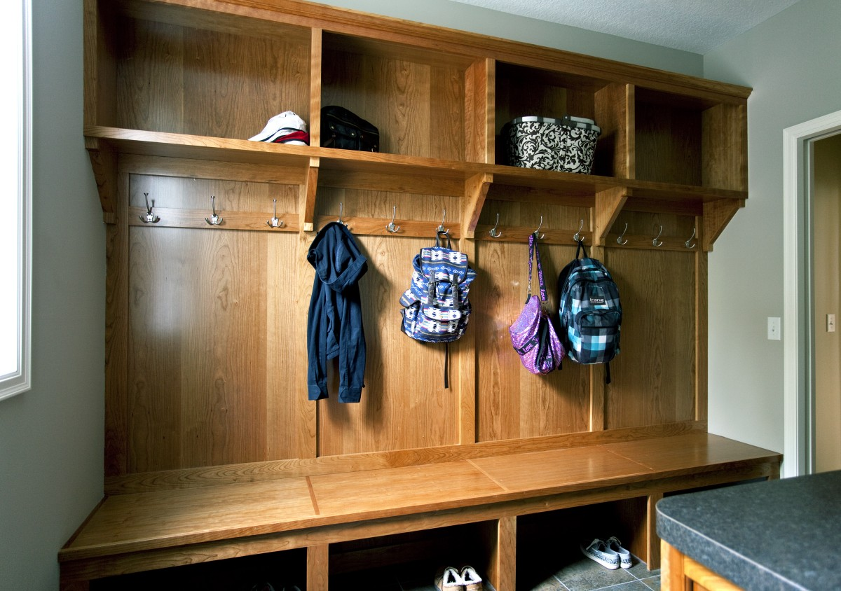 <p>This new mudroom gives the owners and their children a beautiful and comfortable place to unload and clean up and store their things before entering the main part of the home. The focal point of the room is a large custom cherry bench with coat hangers and shelves.</p>