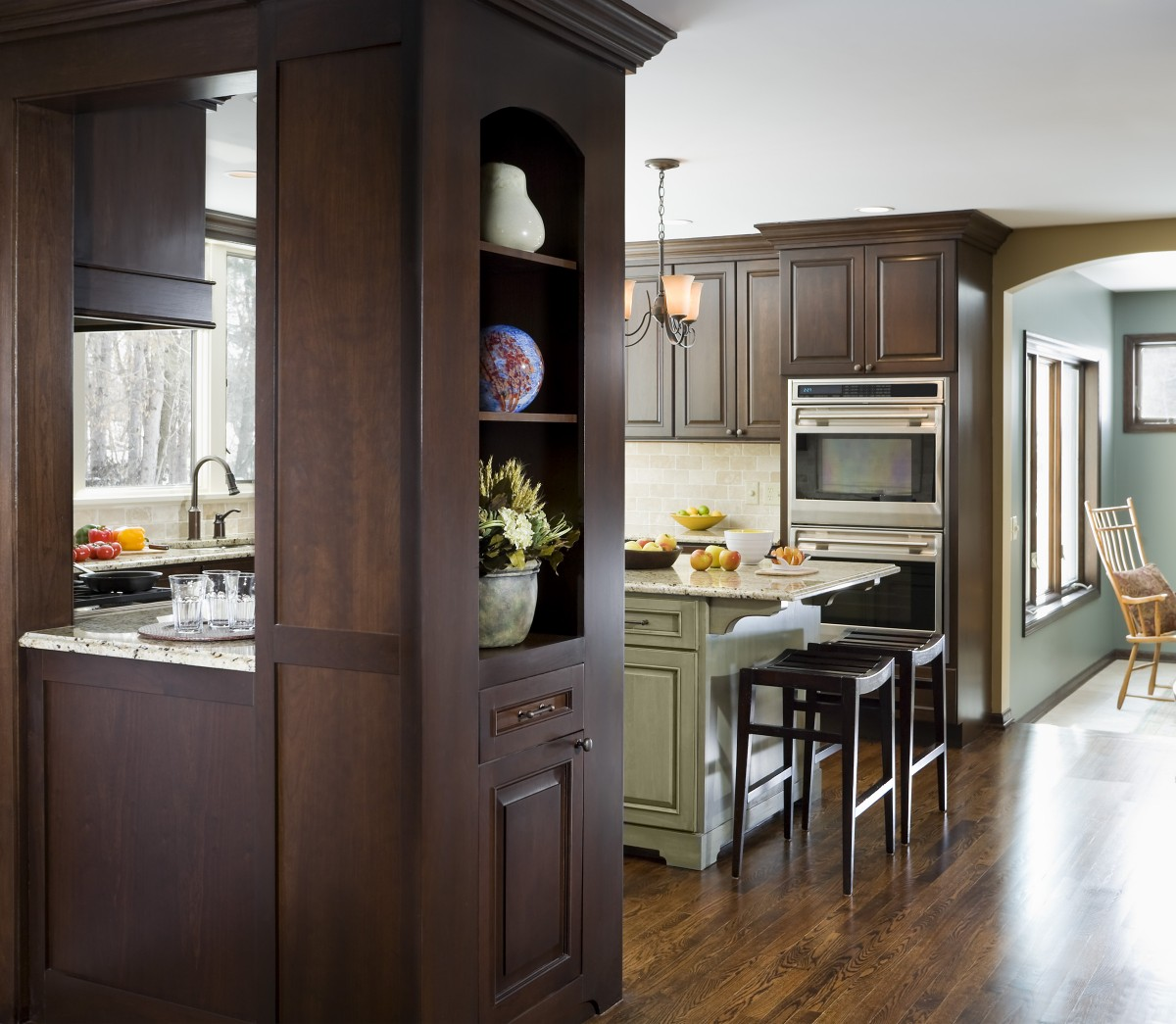 In the kitchen, honey oak cabinets were replaced by dark-stained custom cherry perimeter cabinets and a pigment stained island.  A small addition made the kitchen more spacious, and large new windows provide panoramic views of the wooded lot.
