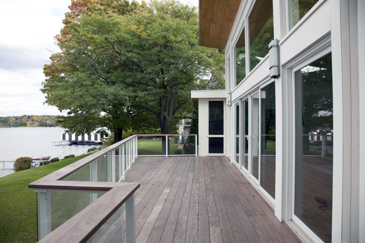 An asymmetrical deck complements the modern butterfly roof. The glass railing guarantees an unobstructed view.