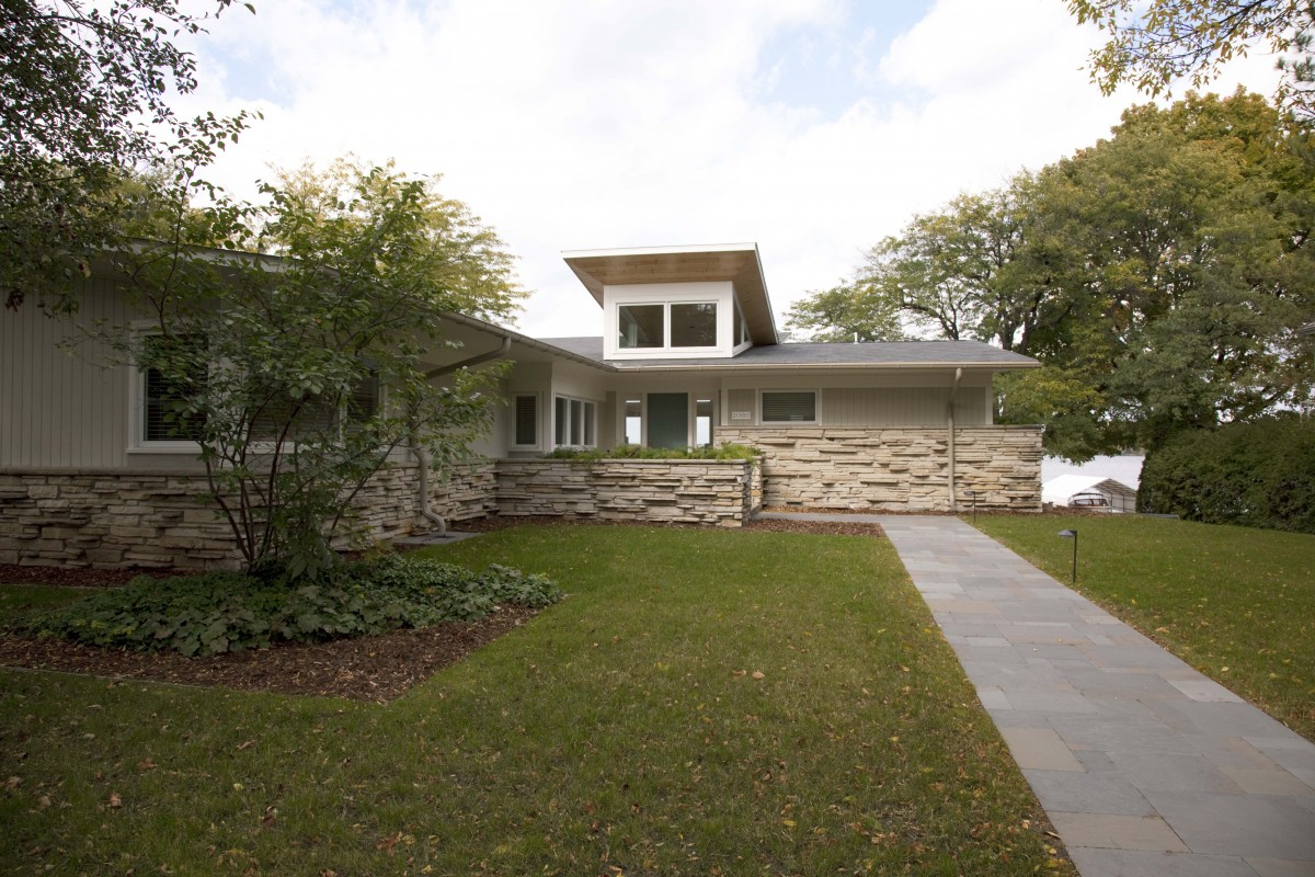 Set along the shores of Lake Minnetonka, this home's new butterfly roof with transom windows creates a modern coastal statement. The pine ceilings carry through to the exterior soffits, creating one continuous plane. Generous windows and a neutral color palette bring nature into the space, further adding to the feeling of modern, simple beach living.