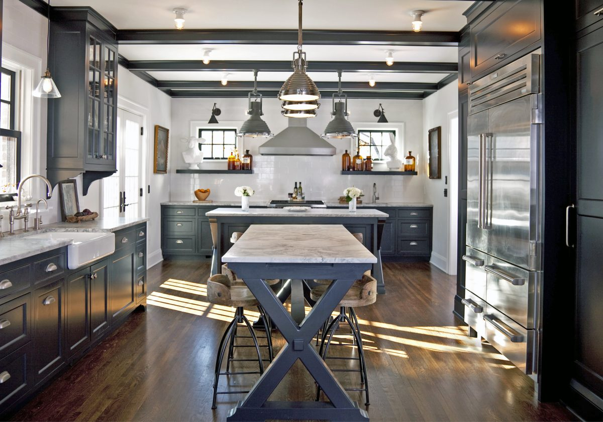 This kitchen's black and white color palette, industrial light fixtures and the owners' unique decorating style combine to striking effect. The kitchen was opened up to the dining area to create better flow in the home's interior, and new french patio doors connect it to the outdoors.