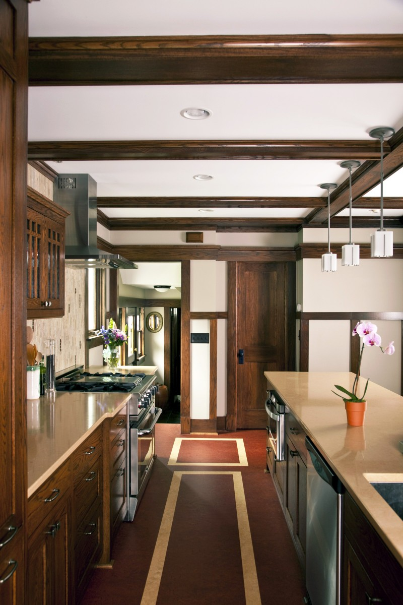 The owners of this 1915 prairie style home desired to expand their kitchen and bring in the authentic old-world detailing of the rest of the home. To this end, the kitchen was opened to the dining area room and a small addition was built. The dining room's beamed ceiling and prairie style woodwork were carried into the new kitchen and oak cabinets were custom built to match existing woodwork and hutches. This project helped the owners make the most of their home and recaptured its original spirit.