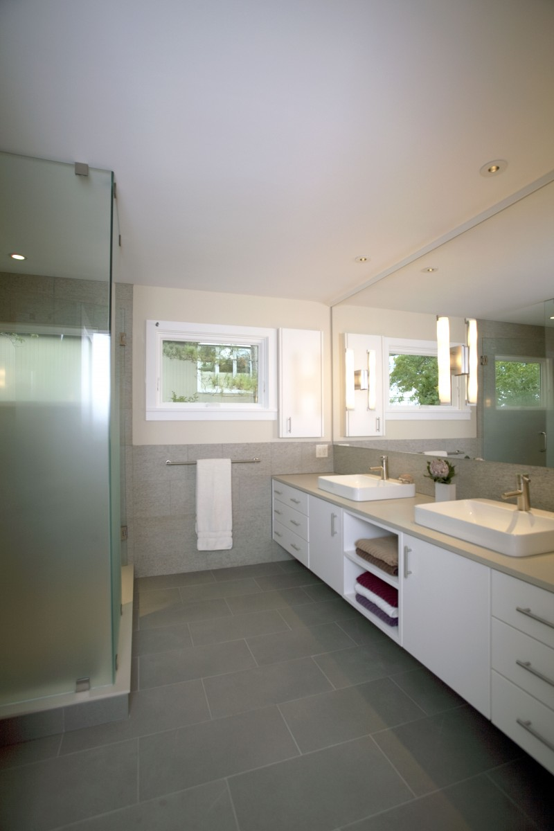 The bathrooms feature clean design and a relaxed color palette, working in harmony with the rest of the home. The master bathroom's shower was installed with gradient-frosted glass for privacy.