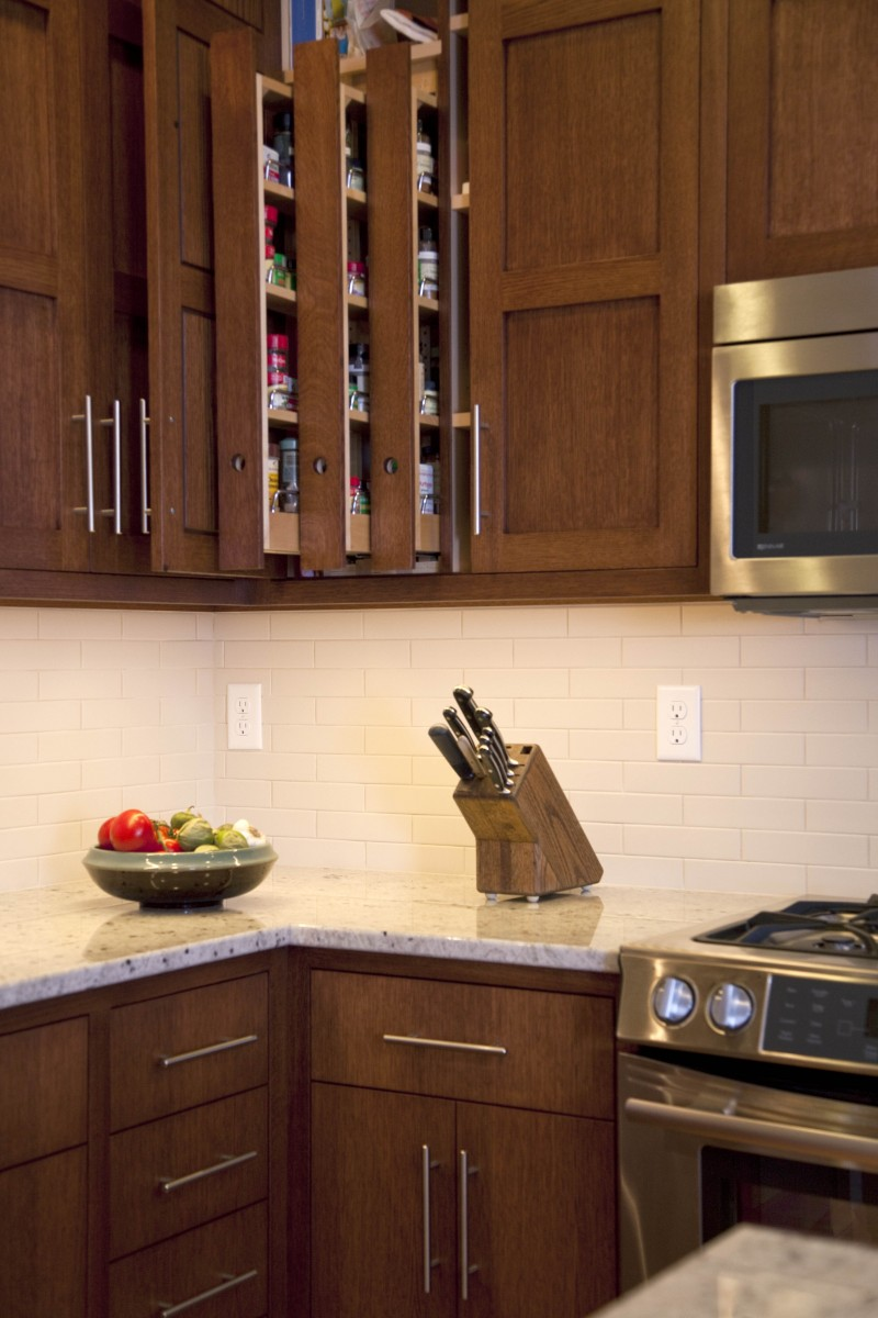 <p>An upper cabinet near the cooking area houses a custom spice rack with three independently-moving pullouts.</p>