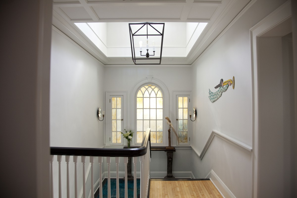 <p>Opening the floor beneath a dormer at the main stairwell increased the amount of daylight coming into the house.  A paneled ceiling was created to highlight and frame the new opening to the dormer above.</p>