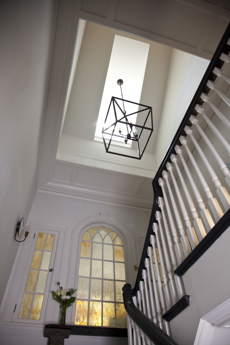 Opening the floor beneath a dormer at the main stairwell increased the amount of daylight coming into the house.  A paneled ceiling was created to highlight and frame the new opening to the dormer above.