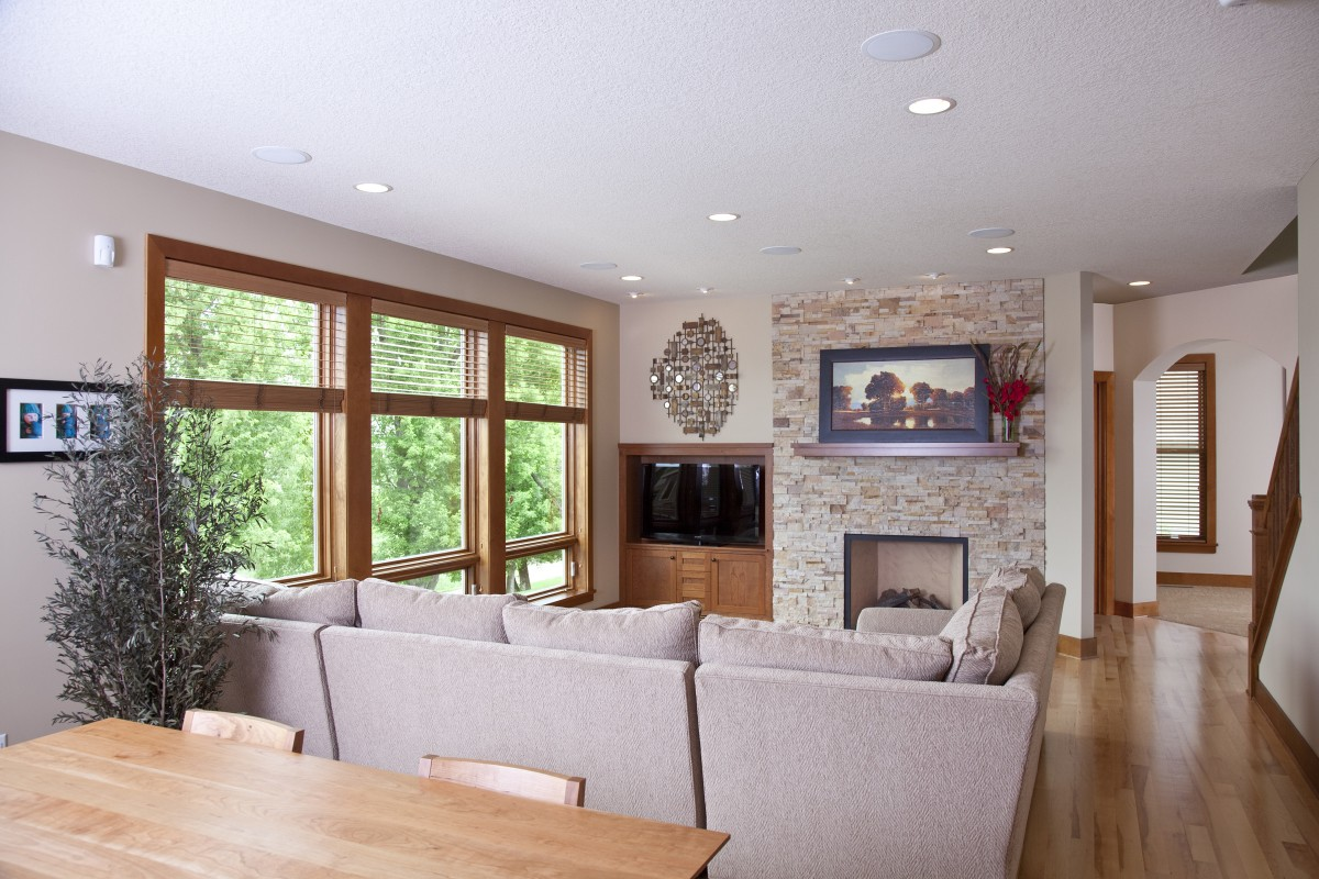 The owners of this 2004 production home wanted to add some character, as well as fix a few issues with layout and flow. The fireplace area underwent a dramatic transformation, with stock cabinets being replaced by custom and the addition of the stone facing around the new gas fireplace.