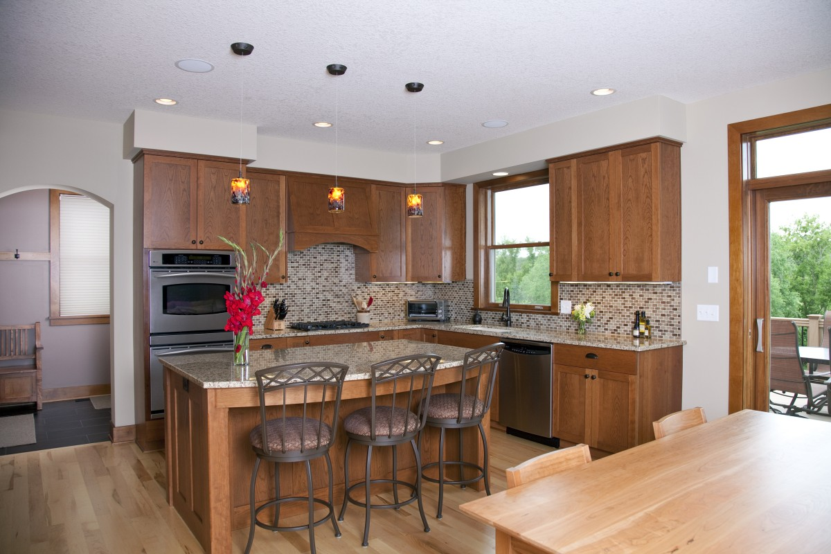 The owners of this 2004 production home wanted to add some character, as well as fix a few issues with layout and flow. New doors were put on existing cabinet boxes, a new custom island was built, and some cabinets were added. New pendants, flooring, granite tops, backsplash and range hood complete the transformation of the kitchen.