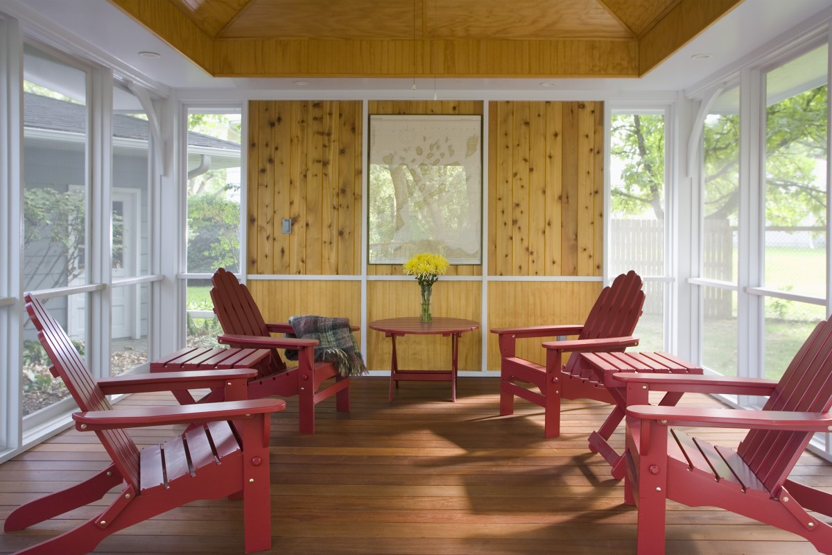 This photo highlights the interplay of materials in the interior of the new porch.  The top portion of the accent wall is knotty pine, while the lower portion and ceiling are clear pine.  These are contrasted with the darker tones of the ipe deck boards and the lighter tones of the white trim.