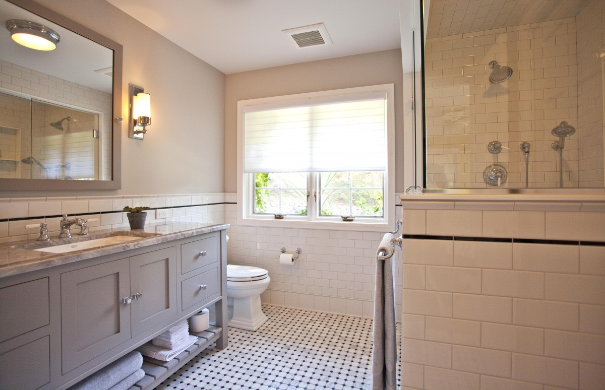 A fresh approach to classic style completely transformed this master bathroom. Soft gray walls, white subway tile and marble flooring exemplify the feeling of casual luxury. The large medicine cabinet and generous vanity with open shelf provide ample storage space.