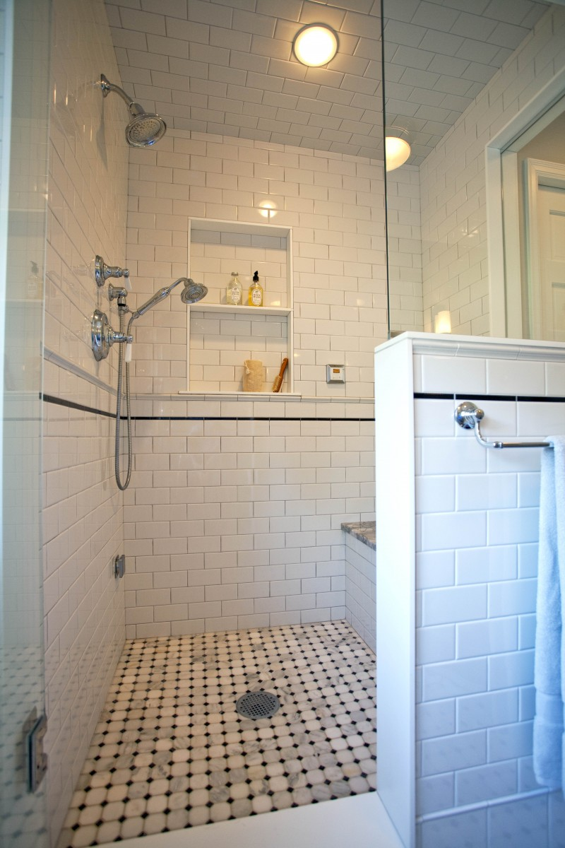 The steam shower has a built-in bench, niche, and secondary hand-held shower.
