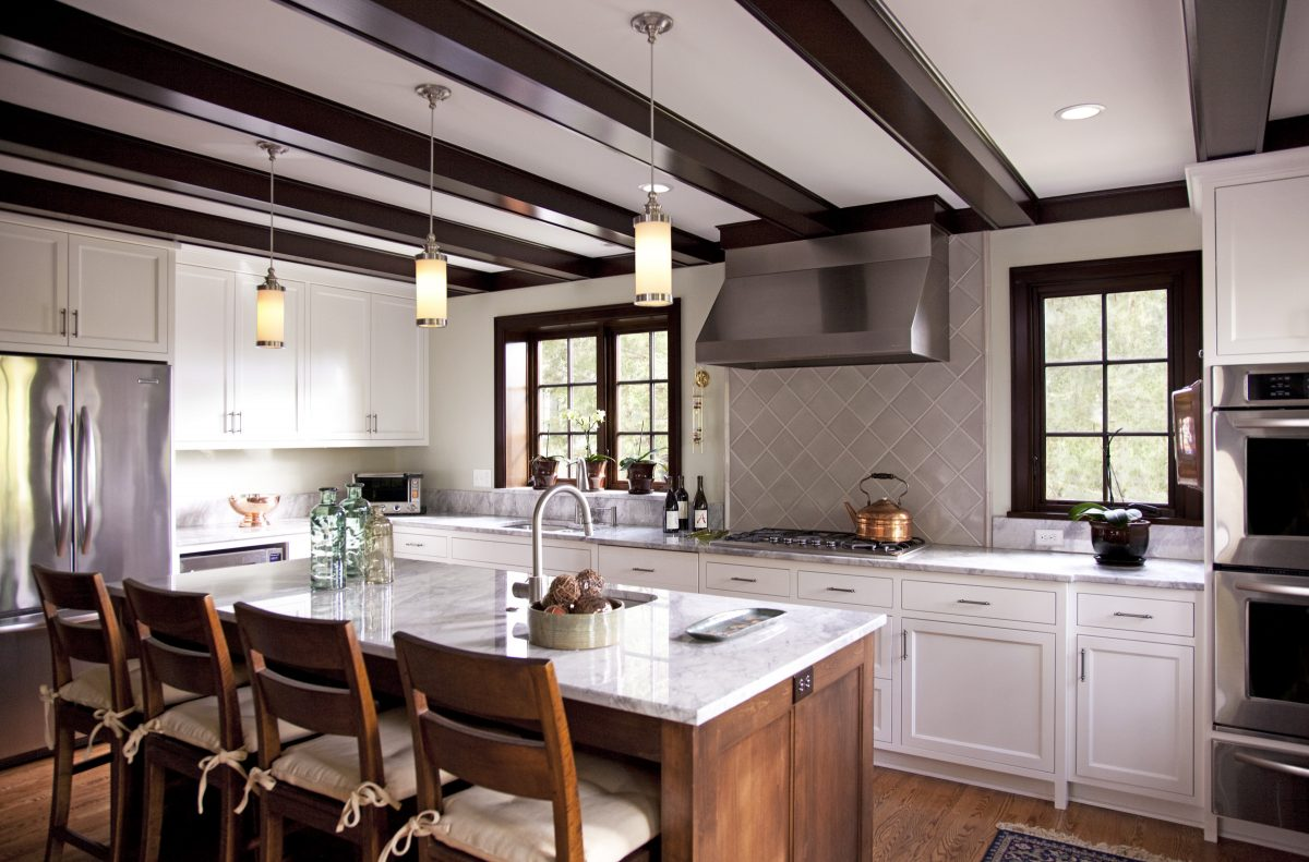 The remodel of this home took place in two phases.  During phase II, the beams in the kitchen were painted to look like the stained alder woodwork present throughout the house.