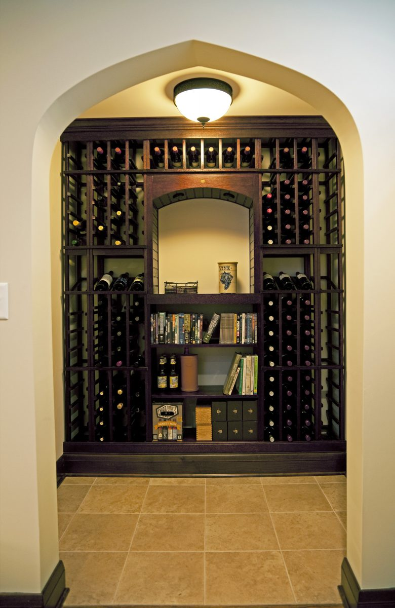 <p>This little wine nook used to be a storage closet. Opening up the entryway connected it to the rest of the newly remodeled basement, then it was just a matter of adding lighting, tile, millwork and shelves for wine storage. It has a 140 bottle capacity, plus a shelf for tasting and storage for books, beer or extra cases of wine.</p>