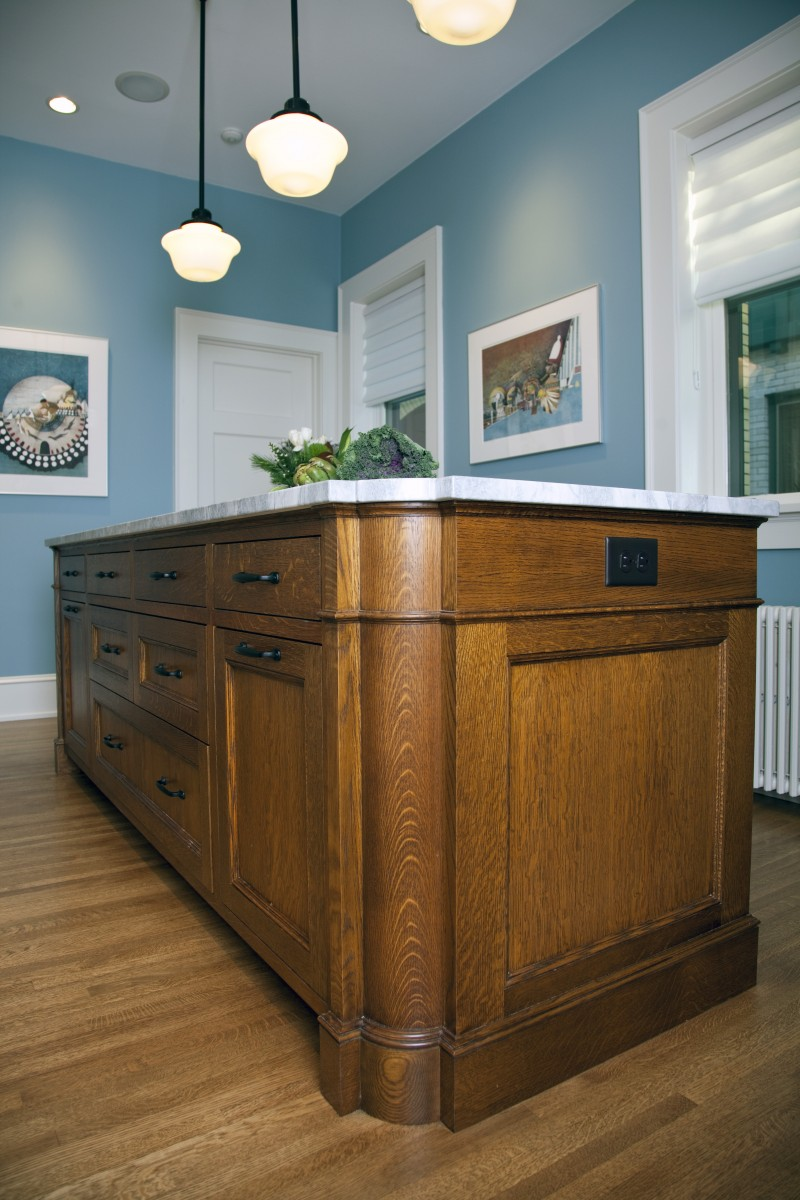 The island and floor are both quartersawn oak, matching the buffet and floors in the rest of this grand old home. The rounded side of the island adds visual interest and imitates the buffet in the dining room.