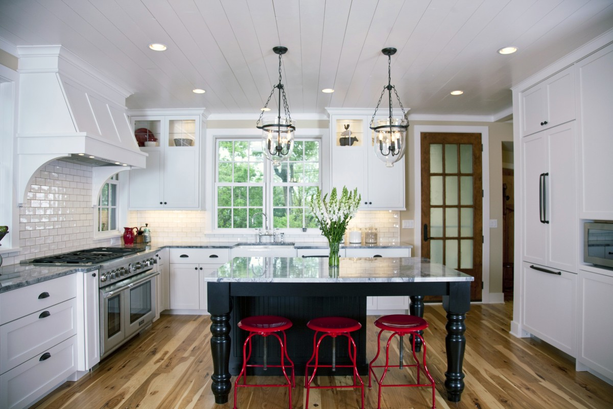 Though the entire home was built in 2012-2013, our designers made it look like a historic lakeside cottage through traditional design and materials. Enameled shiplap boards are present on the ceilings throughout the first floor, as well as on some of the walls, and the floors are hickory, which adds to the old-time aesthetic. The kitchen features custom cabinetry, a traditional subway tile back splash, and plenty of seating and natural light. The owner bought metal stools and had them painted red by a car painter – we think they turned out quite nicely!