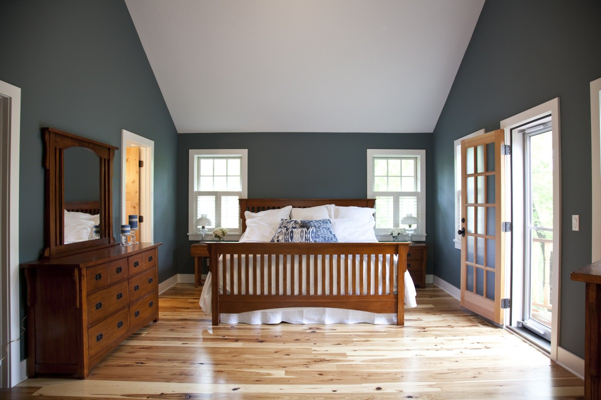 The master bedroom has a high, vaulted ceiling and four windows, making it feel large and light. A door leads out onto a small deck, large enough for two chairs, where the owners can enjoy their morning coffee and a view of the lake.