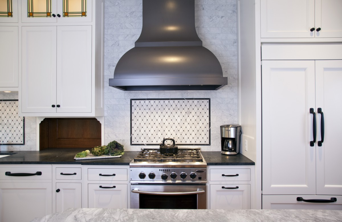 This shot shows some of the thought and detail that went into the kitchen. A custom hood gives a curvy elegance to the space, while the carrera marble backsplash and soapstone countertops add a rich texture. The cabinet front fridge (right) blends seamlessly with the cabinetry, and the stained/leaded glass windows add a pop of color and tie the space in with the originals in the buffet in the dining room.