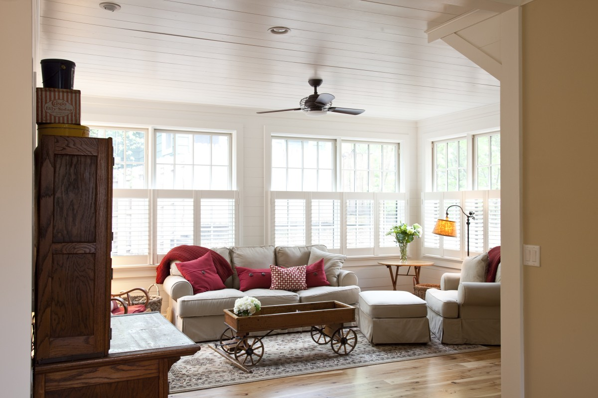 The sunroom is true to its name, with three walls of floor-to-ceiling windows. It is open to the kitchen on one side and to the living room on the other, allowing natural light to penetrate deep into the home. The tongue-and-groove boards present on the ceilings throughout the first floor were carried through onto the walls in the sunroom, giving it a particulaly warm and inviting feel.