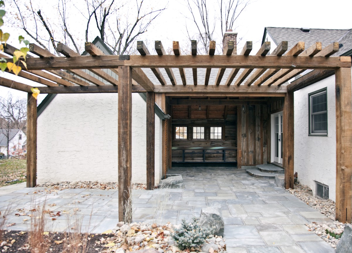 <p>Rustic sophistication aptly describes this new garage and timber frame breezeway. Board and batten siding was crafted from antique reclaimed wood shipped from Montana. Stone slab steps lead to bluestone pavers, which continue onto a pergola-covered patio.</p>
