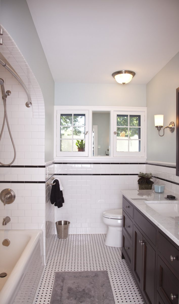 The new guest bathroom includes a custom vanity with a carrera marble top, subway tile, and a heated floor.