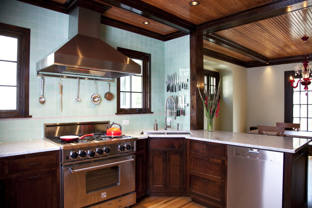 signed for a professional chef, this kitchen is as practical as it is beautiful. Open storage is utilized, providing easy access to dishes and cookware and to expedite the preparation of the latest delicacies. The design incorporates materials and details inspired by the clients' childhood homes and their fondness for vintage diners. Beams and beadboard on the ceiling tie the kitchen and dining room together and rich textures like carrera marble countertops and handcrafted mint green tile add a higher level of refinement and a little spice to this kitchen.